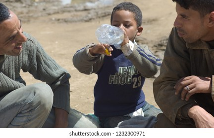 FES - APRIL 16 2010: Berber son drinks from a bottle of water at a market (souk) in a village near Fes in Morocco.
