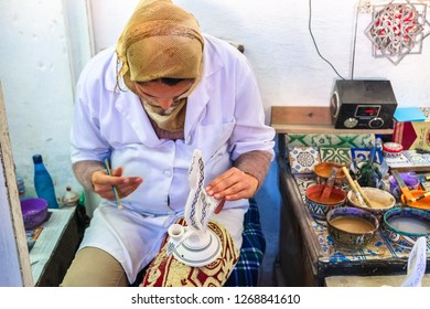 Fes el Bali, Morocco. March 16, 2014 : A Moroccan woman paint on a ceramic pottery. Medina of Fez.