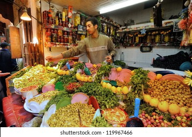 FES - MARCH 10: Unknown man trades a green olives in a Market (souk) in a city Fes in Morocco. The market is one of the most important attractions of the city. March 10, 2012 Fes, Morocco.