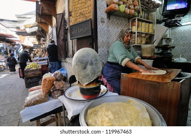 FES - MARCH 10: Unknown woman trades a traditional bread in a Market (souk) in a city Fes in Morocco. The market is one of the most important attractions of the city. March 10, 2012 Fes, Morocco.