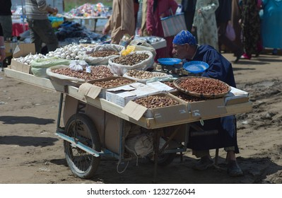 FES, MOROCCO - APRIL 16 2010: Old man with blue djellaba sells his merchandise of all kinds of nut, dates and garlic on a wooden plate on a handcart
