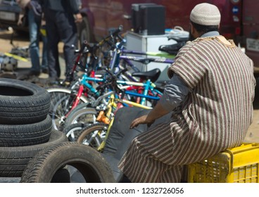 FES, MOROCCO - APRIL 16 2010: Man in djellaba at a market (souk) in a village near Fes in  Morocco. Man sells bicycles and car tires