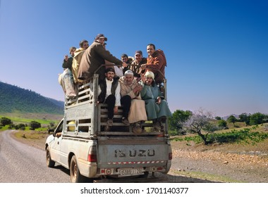 FES, MOROCCO - FEB 09: Unidentified morrocan men ride in a back of a truck on the road and pose for a camera on February 09, 2020 in Fes (Fez) region, Morocco, Maghreb, North West Africa