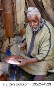FES, MOROCCO - FEB 13, 2019 - Metalworker uses ball peen hammer to form copper dish in the medina of Fes, Morocco, Africa