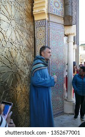 FES, MOROCCO - FEB 13, 2019 - Tour guide in jellaba in front of massive doors of the National Palace, Fes, Morocco, Africa