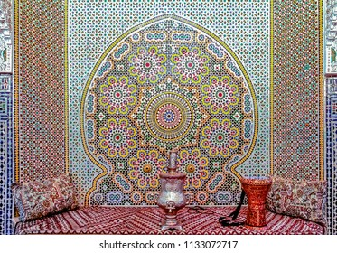 Fes, Morocco - May 11, 2013: Courtyard decorated with ornate mosaic, with traditional couches, a samovar and a drum in a Moroccan riad