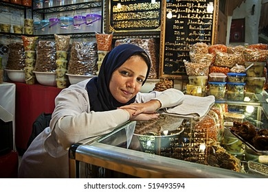 FES, MOROCCO - NOVEMBER 8, 2016: Young lady selling spices and nuts inside the market in the Medina of Fes.