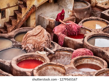 FES, MOROCCO, OCTOBER 19, 2018: A worker trims a pile of leather hides with a sharp knife after being dyed in the leather tannery in the old city of Fes in Morocco.