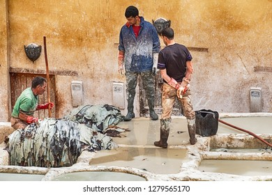 FES, MOROCCO - OCTOBER 19, 2018: Three workers in the Chouara leather tannery in Fes, Morocco soak animal skins in the tanning pits to soften the leather.