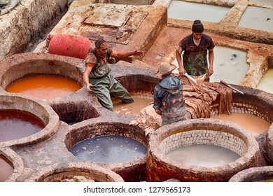 FES, MOROCCO, OCTOBER 19, 2018: Three men talk while standing in the tanning and dye vats while working in the Chouara leather tannery in Fes, Morocco.