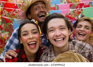 Festa Junina: June Party. Happy people in plaid costume at traditional holiday. Flags and decor in background.