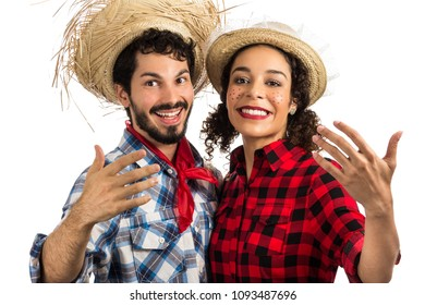 Festa Junina: party in Brazil in the month of june. Brazilian couple wearing plaid shirts. Man and woman dressing checked pattern clothes waving hands to invite to party.