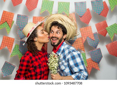 Festa Junina: party in Brazil in the month of june. Man and woman dressing checked pattern clothes. Woman kissing man holding flowers.
