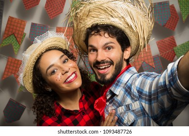 Festa Junina: party in Brazil in the month of june. Man and woman dressing checked pattern clothes. Man and woman dressing checked pattern clothes are taking a selfie photo.