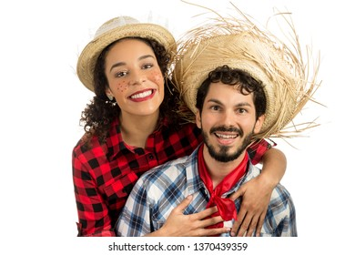 Festa Junina: party in Brazil in the month of june. Brazilian couple wearing plaid shirts. Man and woman dressing checked pattern clothes smiling and looking at camera.