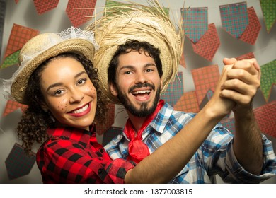 Festa Junina: party in Brazil in the month of june. Man and woman dressing checked pattern clothes. Man and woman dressing checked pattern clothes hold hands and dance together.