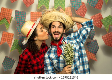 Festa Junina: party in Brazil in the month of june. Man and woman dressing checked pattern clothes. Pretty woman is kiising happy man. He is holding flowers.