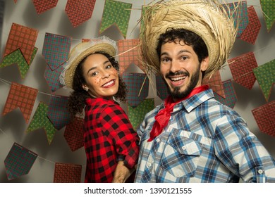 Festa Junina: party in Brazil in the month of june. Man and woman dressing checked pattern clothes. Man and woman dressing checked pattern clothes dance quadrilha style. Smiling.