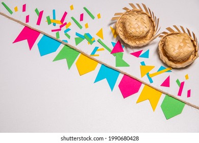 Festa Junina theme background. Little flags hanging on a rope. Confetti and two tradicionals brazilian straw hats. White background. Mockup invitation card.