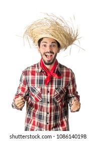 Festa Junina is a traditional brazilian party celebrated in june. Man wearing plaid shirt (red, black, white) and straw hat, costume as Caipira. Goal, celebrating, football.