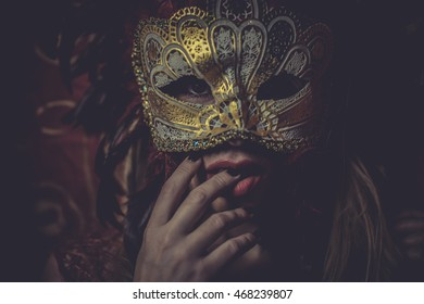 Festival, Blonde with gold mask on red cloth embroidered golden thread, mystery and sensuality
