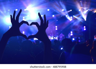 Festival crowd raising hands in music concert front of bright stage lights