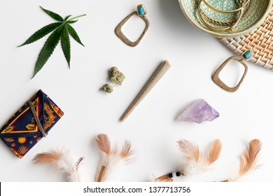 Festival items laid out with a Joint, Marijuana Buds, Earrings, Feathers, and a Crystal
