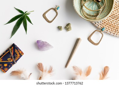 Festival items layed out with a Joint, Marijuana Buds, Earrings, Feathers, and a Crystal