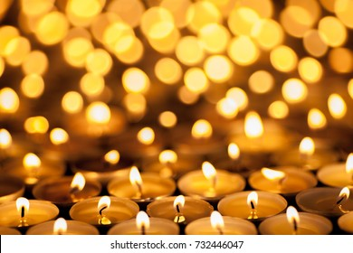 Festival of Lights. Beautiful candlelight. Selective focus on foreground of many burning tealight candles. Diwali or Christmas celebration image.