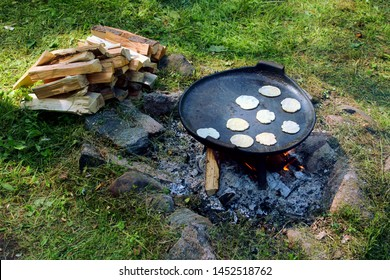 Festival of Medieval Culture. Medieval Reenactment. Freshly cooked food on a fire in the forest. Restoration of old Viking traditions. Top view of the pot of pea pancake.