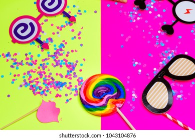 Festival party or carnival border of lollipop, paper cute glasses, lip and Multi-color confetti on yellow pink background with copy space. Holi and ugadi holidays, birthday invitation card concept.