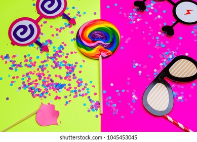 Festival party or carnival border of lollipop, paper cute glasses, lip and Multi-color confetti on yellow pink background with copy space.