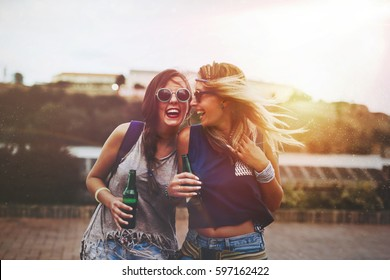 Festival party girls in summer having fun and drinking