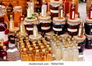 Festival of street food. Wooden counter with a variety of bottles with alcoholic and fruit drinks and homemade jams sold outdoors in the local market