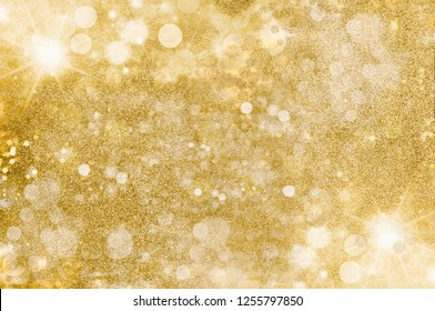 Festive abstract gold background. Golden Christmas background with sparkling and twinkling bokeh from party lights and golden glitter, full frame copyspace for your seasonal greeting