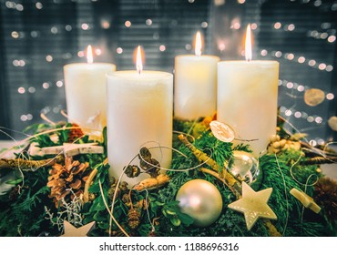 festive advent wreath with four burning candles and beautiful background bokeh