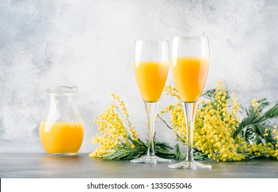 Festive alcohol cocktail mimosa with orange juice and cold dry champagne or sparkling wine in glasses, gray bar counter background with flowers, place for text, selective focus