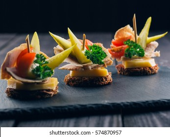 Festive Appetizer with bread, meat, tomatoes and cucumber on black background