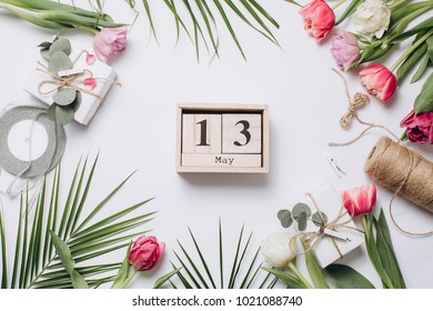 Festive arrangement: boxes with gifts, ribbons, calendar with thirteenth day of May to the mother's day and tulips with palm leaf on a white table, top view.