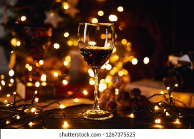 Festive atmosphere in the evening with a glass of red wine. Light bokeh on background. Christmas, New Year's or Saint Valentine holiday. Golden color and soft focus.