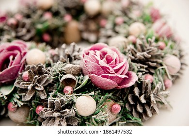 Festive background with an Advent wreath. Christmas mood. Handmade decoration with flowers and frost. Natural pink - purple color.