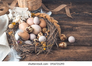 Festive background with beautiful quail and chicken eggs on a wooden background with vintage tinting. Eggs of natural color from the nest.