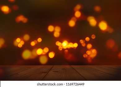 festive background with blurry lights, empty wooden table in foreground with bright candlelight bokeh on dark blurred backdrop, celebration at night concept