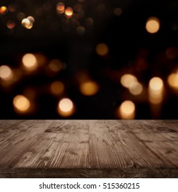 Festive background for celebratory moments and a concept in front of a empty wooden table with golden bokeh