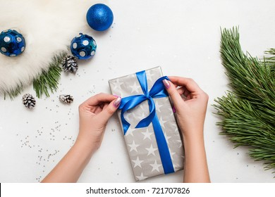 Festive background of Christmas present decoration. Unrecognizable woman wrapping gift box, ornament blue balls and pine branch laying on table nearby, top view with copy space. Handmade decor concept