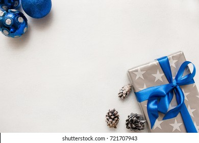 Festive background of Christmas presents. Wrapped gift box, ornament blue balls and strobila laying on white table nearby, top view with copy space. Handmade decor concept