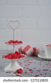 Festive background.  Coffee cup, white two tier serving tray full of multicolor sweet sprinkles sugar candy hearts and packing Valentine's  Day gifts  Love and Valentine's day concept.