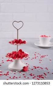 Festive background.  Coffee cup, white two tier serving tray full of multicolor sweet sprinkles sugar candy hearts.  Love and Valentine's day concept decoration