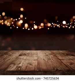 Festive background with golden bokeh effects and empty wooden table for a christmas decoration