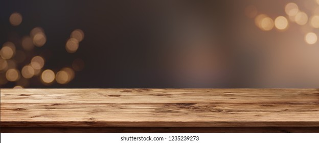 Festive background with golden bokeh and empty rustic wooden table for christmas decorations